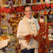 Cheerful woman buying Christmas tinsel garland — Стоковая фотография