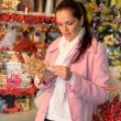 Woman buying Christmas ornaments in shop — Stock Photo
