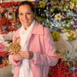 Smiling woman shopping Xmas decorations in shop — Stock Photo #31303901