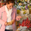 Woman putting Xmas decorations to shopping basket — Stock Photo