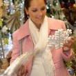 Smiling woman customer buying snowflake ornament — Stock Photo #31303929