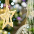 Gold star ornament hanging from Christmas tree — Stock Photo