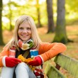 Smiling teenager girl sitting autumn park bench — Stock Photo
