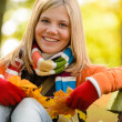 Autumn cheerful young girl sitting park fall — Stock Photo
