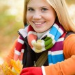 Smiling young girl autumn colorful scarf leaves — Stock fotografie