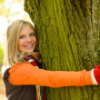 Smiling teenager girl embracing tree autumn woods — Stock Photo