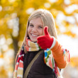 Smiling autumn teenager girl thumbs up forest — Stock Photo