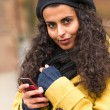 Woman with cell phone in fall nature — Stockfoto