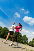 Low angle view of couple running outdoors — Stock Photo