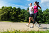 Portrait of fit couple running outdoors — Stock Photo