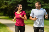 Cheerful Caucasian couple running outdoors — Fotografia Stock