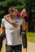 Smiling man giving piggyback ride his girlfriend — Stock Photo