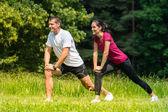 Kadın ve erkek atlet açık havada germe — Stok fotoğraf