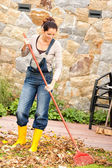 Smiling woman raking leaves fall housework garden — Stock Photo