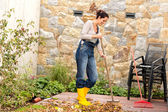 Young woman sweeping autumn leaves veranda — Stock Photo