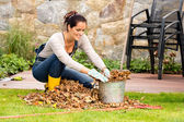 Smiling woman stuffing leaves pail autumn gardening — Stock fotografie
