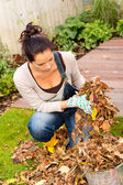 Young woman autumn gardening cleaning leaves — Stok fotoğraf