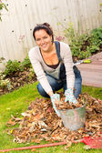 Happy woman filling bucket leaves fall gardening — Stock fotografie