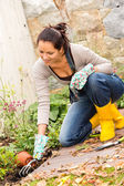 Smiling woman plant flowerbed hobby garden autumn — Stock Photo