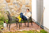 Happy woman relaxing autumn patio drinking tea — Stock Photo