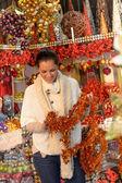 Lachende vrouw met kerst klatergoud bij shop — Stockfoto