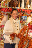 Happy woman shopping Christmas tinsel ornaments — Photo