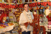Cheerful woman buying Christmas tinsel garland — Stok fotoğraf