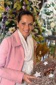 Junge frau kaufen glitzernde weihnachtskranz — Stockfoto