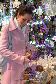 Happy woman buying sparkling Christmas decorations — Stock Photo
