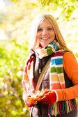 Sunny autumn smiling girl holding dry leaves — Stock Photo