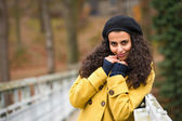 Young woman standing autumn park yellow coat — Stock Photo