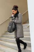 Woman leaving office making phone call — ストック写真