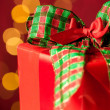 Christmas gift and sparkling lights in background — Stockfoto