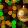 Christmas ball hanging defocused sparkling lights — Stock Photo
