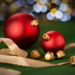 Red Christmas baubles & gold jingle bell — Stock Photo