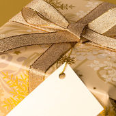Gold Christmas present with blank tag wishing card — Stock Photo