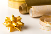 Golden wrapping paper and bow present decoration — Stock Photo
