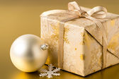 Christmas present and bauble on gold background — Stock Photo