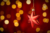Hanging Christmas Ornament star lights background — Stock Photo