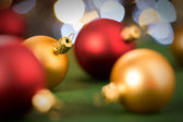 Gold and red christmas baubles on green — Stock Photo