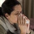 Stock Photo: Ill womsneezing in tissue