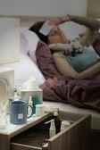 гриппа лекарства на тумбочке больной женщине — Стоковое фото