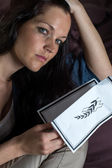 Portrait of young widow holding obituary — Stock Photo