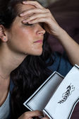 Crying young woman holding obituary — Stock Photo