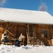 Stock Photo: Cozy wooden cottage winter snow people outside