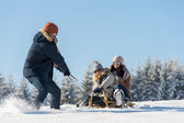 Young man pulling girls on winter sledge — Stock Photo