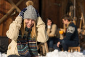 Young woman in winter hat snow cottage — Stock Photo