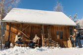 Cozy wooden cottage winter snow people outside — Stock Photo