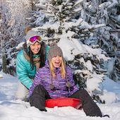 Two female friends on bobsleigh winter snow — Stock Photo