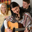 Young friends in winter cottage play guitar — Stock Photo